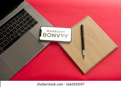 Tula, Russia - February 07, 2020: Logo Marriott bonvoy on a smartphone near modern laptop on red background