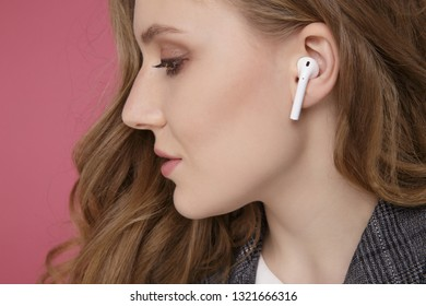 Tula, Russia - JANUARY 24, 2019: Happy woman listening music Apple AirPods wireless .
