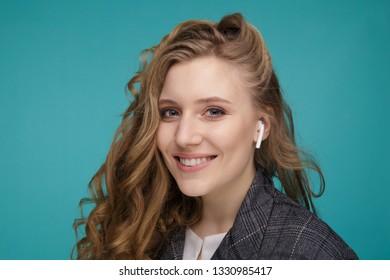 Tula, Russia - JANUARY 24, 2019: Happy woman listening music Apple AirPods wireless .
