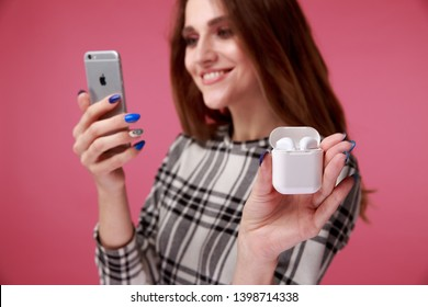 Tula, Russia - JANUARY 24, 2019: Happy woman listening music Apple AirPods