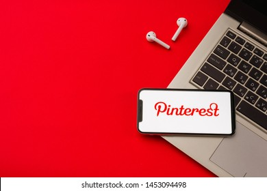 Tula, Russia - May 24,2019: Apple iPhone X and Airpods on desk with Pinterest application on the screen. Pinterest is an online pinboard that allows people to pin  interesting things. Red backgro