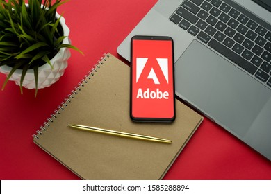 Tula, Russia, november 26, 2019: Adobe logo on the smartphone screen is placed on the Apple macbook keyboard on red desk background.- Image