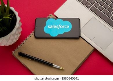 Tula, Russia - october 19, 2019: Logo Salesforce.com displayed on a smartphone near modern laptop on red background