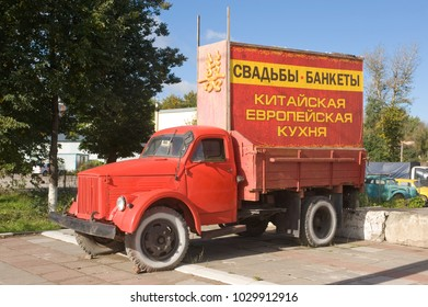"TULA, RUSSIA - September 9, 2012: Advertising Soviet old red truck GAZ-51 with the words ""Wedding Banquets, Chinese, European cuisine"" and the building"