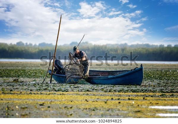 TULCEA, ROMANIA - Sept 2, 2017. Local Fisherman (lipovean minority) netting fish in Danube Delta, Romania