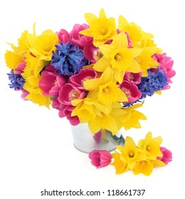 Tulip, daffodil and hyacinth spring flower arrangement in an aluminium pot over white background.
