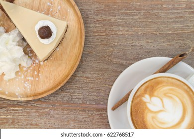 Tulip Flower or Rosette, Latte Art on Top Hot Coffee Cup with Cinnamon Stick on Ceramic Plate and Horlick Cold Layer Cake with Whip Cream on Wood Tray on Wooden Table, Copy Space, Idea Concept Menu.