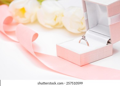 tulip and gold engagement ring on a white background