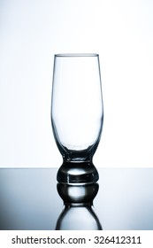 A Tulip Shaped Pint Glass on glass table and white background