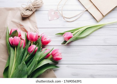 Tulips bouquet. Florist workplace background. Pink flowers, tools set on wooden table. Preparation for the creation of bunch. Floristry, Decorator, diy, craftsmanship, spring gift concept.