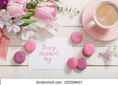 Tulips  and cup of coffee with dessert on white background. Concept mother's day top view