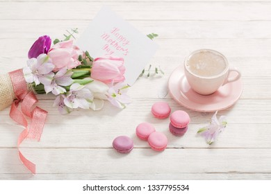 Tulips and cup of coffee with dessert on white background. Concept woman's or mother's day top view