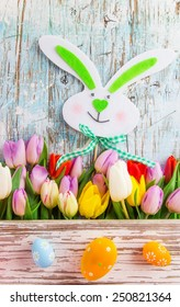 tulips and easter eggs on wooden background, close-up. - Shutterstock ID 250821364