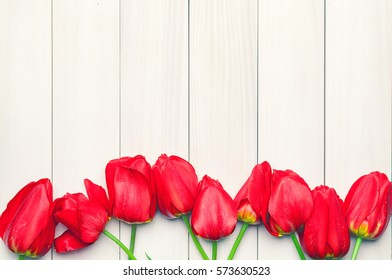 Tulips. Easter. Red tulips on a background of light boards. Spring flowers. Easter 2016. Springtime. Vintage processing. Space for text. Toned image.