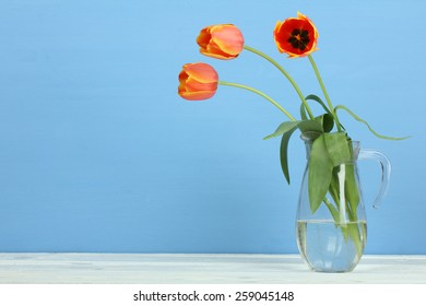 tulips in a jar on a wooden background