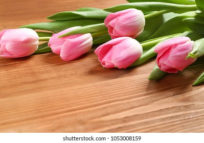 tulips lie on a wooden table