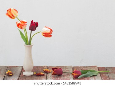 tulips in vase on white old background