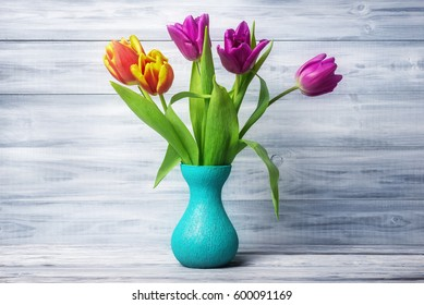 Tulips in vase on wooden background