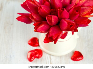 tulips in vase on wooden surface and chocolate hearts