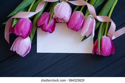 tulips with white card on a wooden background