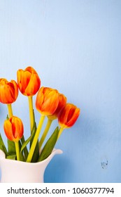 Tulips in a white jug on a wooden background. Beautiful spring bouquet.
