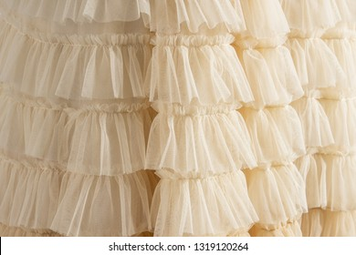 Tulle beige luxury dress with ruffles. Closeup detailed background.