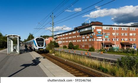 Tullinge, Sweden - August 12, 2015: Tullinge train station, local train arrives to the station, travelers waiting on the platform