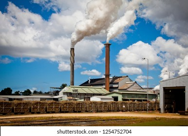 Tully Sugar Mill in Far North Queensland Australia. Chimneys blow thick smoke in front of railway carrying sugar cane into the factory.