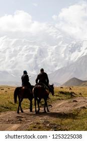 Tulpar, Kyrgyzstan August 21 2018: Two Kyrgyz riders ride their horses to base camp at the foot of Peak Lenin in Kyrgyzstan