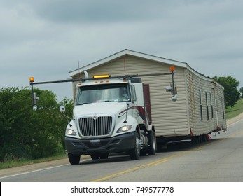 TULSA, OKLAHOMA—APRIL 217: Close up side view of a a trailer truck transporting a mobile home on the road toward Tulsa on a bright day.