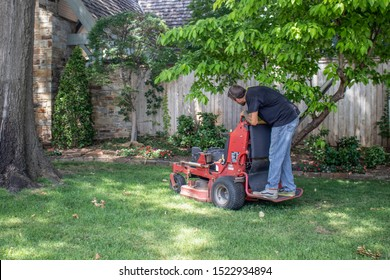 Tulsa USA 6 22 2018 Man with tattoos on standing commercial lawnmower cutting a close circle around tree and flowerbeds in upscale neighborhood - selective focus