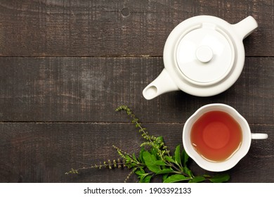 Tulsi or holy basil tea in white cup and teapot with fresh tulsi branch on wooden background top view. Ayurvedic medicine in India.