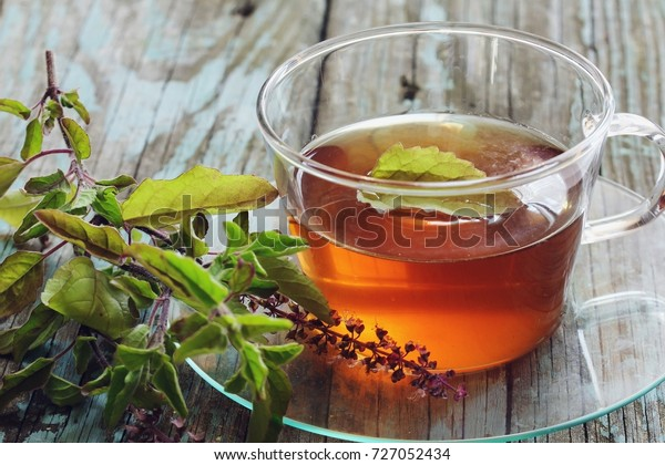 Tulsi Tea served in a cup with fresh leaves on the side, selective focus