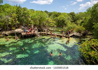 Tulum, Mexico - 05-03-2018: Cenote Azul blue lagoon water with tourists and Mexican people