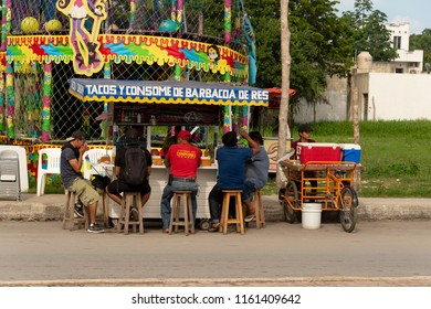 Tulum, Mexico - 7 August 2018: People eating tacos at a colorful mexican food stand.