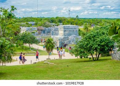 TULUM, MEXICO - JANUARY 10, 2018: Unidentified tourists walking in Mayan Ruins of Tulum Besides Caribbean Sea. Riviera Maya, Traveling America