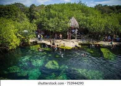 Tulum Mexico - March 10 2017: People bathe in the cenote. Cenote - natural lagoon with transparent turquoise water surrounded by rocks and tropical vegetation. Wild jungle