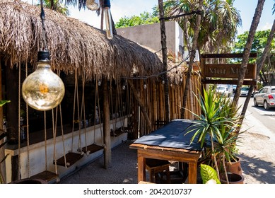 Tulum, Mexico. May 25, 2021. Swing seats at exterior of Mur Mur restaurant with straw roof. Beautiful Mexican resort