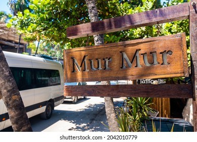 Tulum, Mexico. May 25, 2021. Wooden Mur Mur restaurant name sign hanging on side of road with vehicles