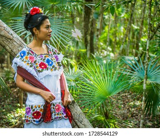 Tulum, Quintana Roo/ Mexico- February 24,2020: a beautiful Mexican woman waiting in the jungle in her huipil dress, a traditional costume of Yucatán