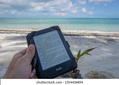 Tulum, Yucatan/Mexico - December 17 2016: Reading a Kindle on a sunny beach in Mexico.