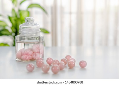 Tumbled rose quartz stones are placed inside of a glass jar with drinking water. It is a gem elixir preparation. Several beads lie in the foreground out of focus.