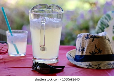 A tumbler and pitcher of Lemonade,  Along with a woven hat and a pair of sunglasses.