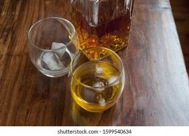 Tumbler of spirits on the rocks with a second empty glass with ice alongside a bottle of alcohol, possibly whiskey, scotch or bourbon