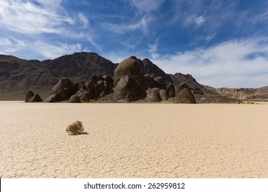 Tumbleweed on dry lake floor with cracked mud, mountains and sky with clouds. Racetrack Playa. Death Valley national park. California.