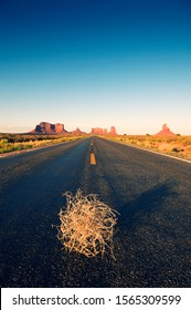Tumbleweed rolls along an empty straight road disappearing over the horizon dotted with iconic sandstone mesas of America's wild west