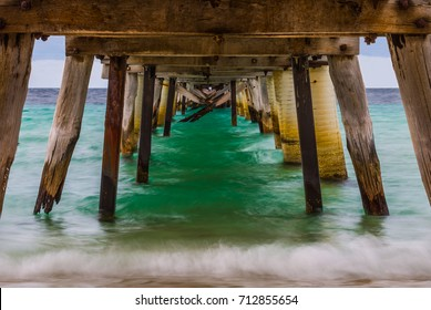 Tumby Bay Jetty, old timber structure, South Australia, Eyre Peninsula, blue green ocean water lapping.