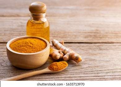 Tumeric ( curcumin, curcuma longa Linn) powder in wooden bowl and  spoon with root and bottle of turmeric essential oil extracted isolated on old wood table background. Beauty and spa concept.