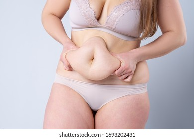 Tummy tuck, flabby skin on a fat belly, plastic surgery concept on gray background