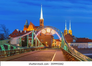 Tumski Bridge and Island with Cathedral of St. John and church of the Holy Cross and St. Bartholomew at night in Wroclaw, Poland